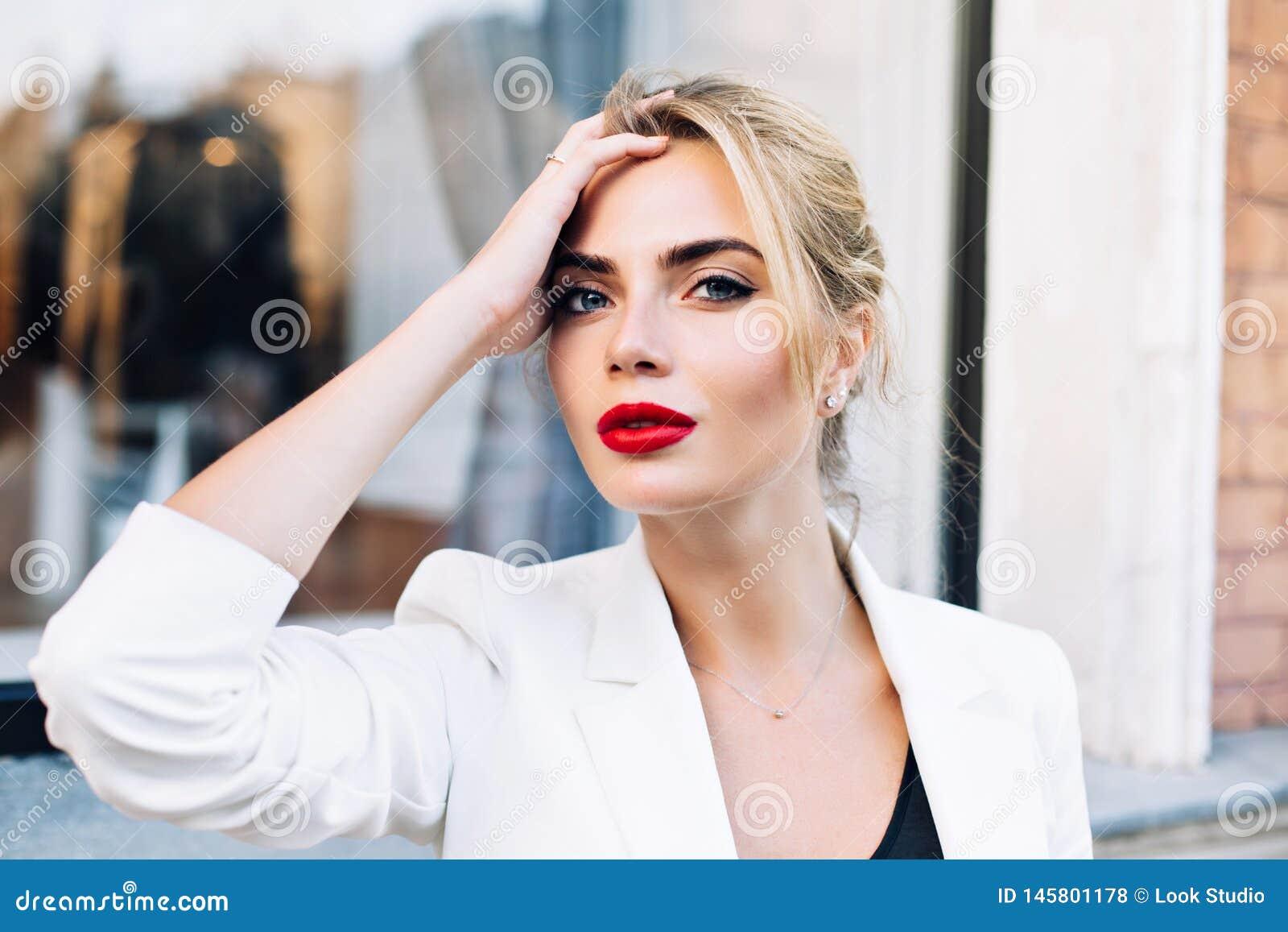 Mujer atractiva del retrato del primer con los labios rojos en la calle Ella lleva la chaqueta blanca, tocando el pelo, mirando a