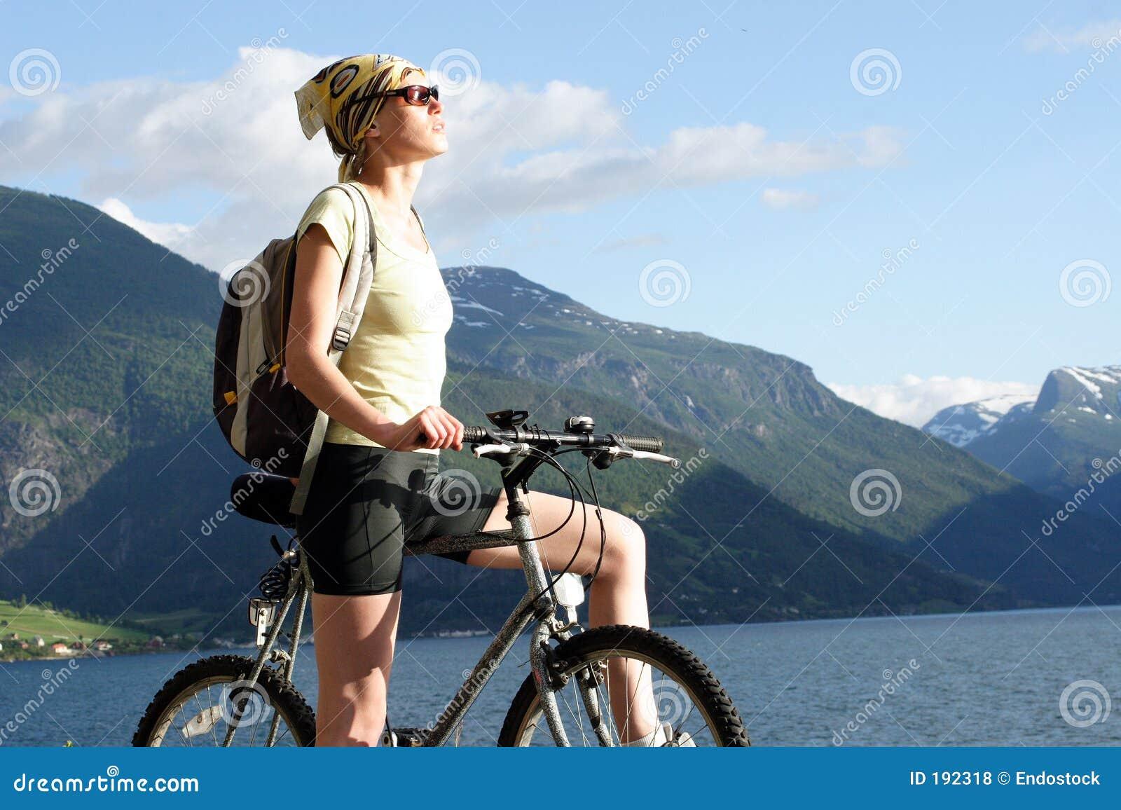 Mujer atractiva en la bici en las montañas