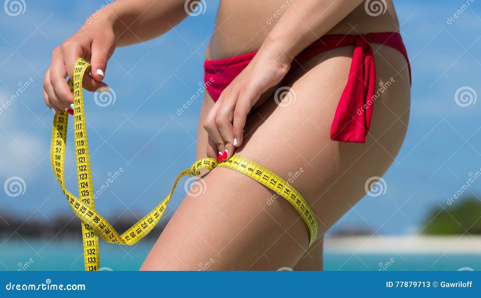 Mujer Atractiva En La Playa En Bikini Con La Cinta De La Medida El Concepto Foto de archivo