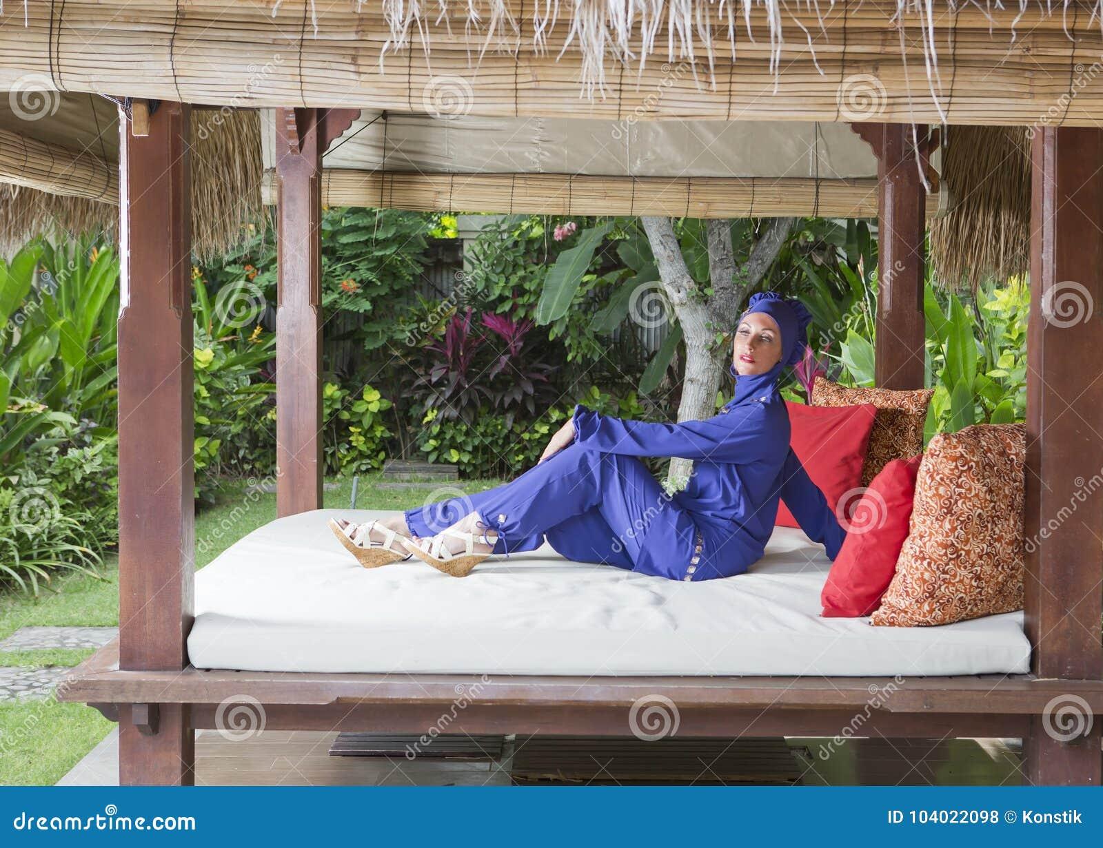 Mujer atractiva en un burkini musulmán del traje de baño en el gazebo para el resto en un jardín