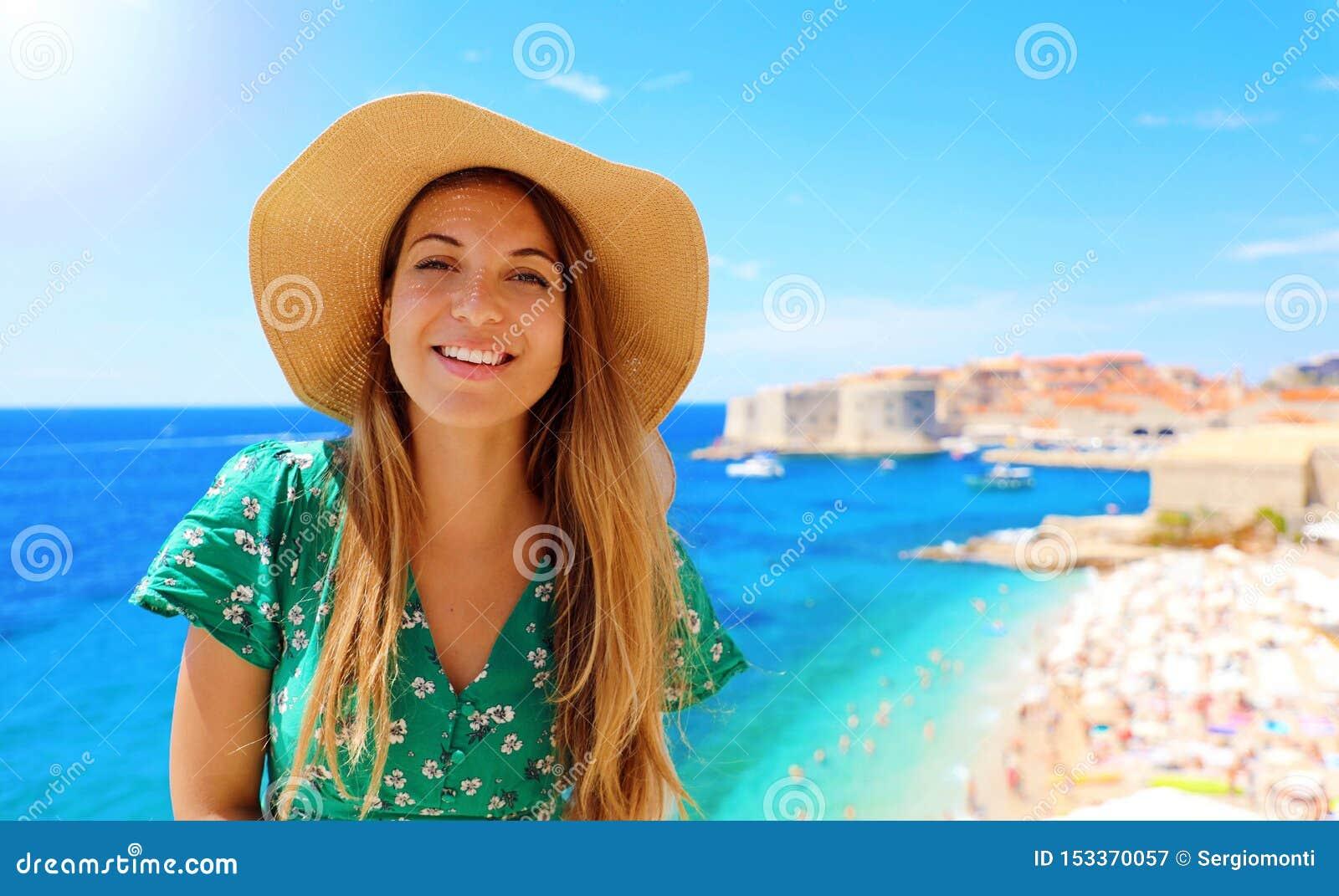 Mujer atractiva feliz del viajero en Croacia con la ciudad y el mar Mediterráneo viejos en el fondo, Europa de Dubrovnik