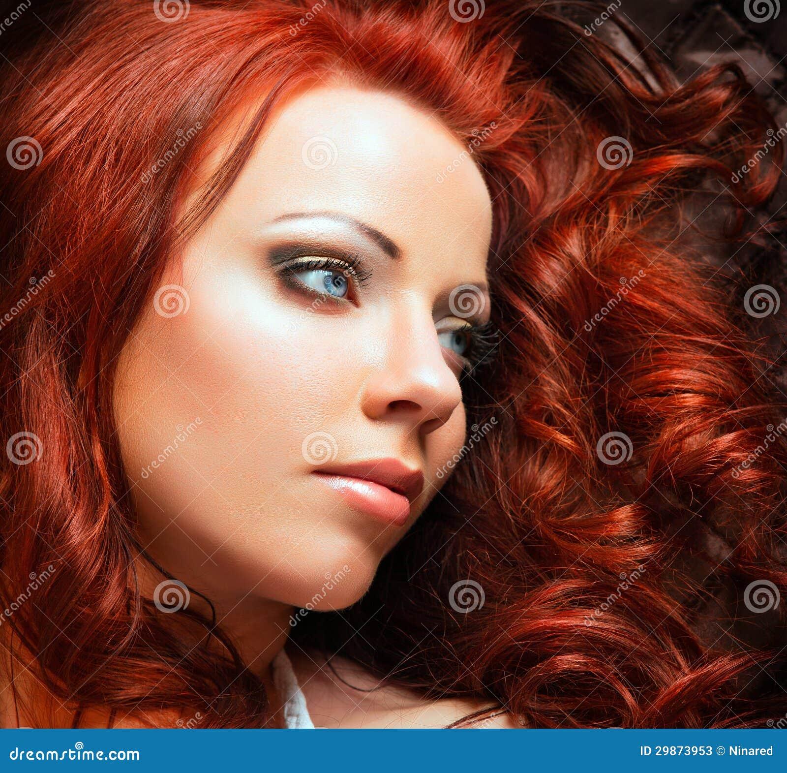 Mujer atractiva hermosa con el pelo rojo