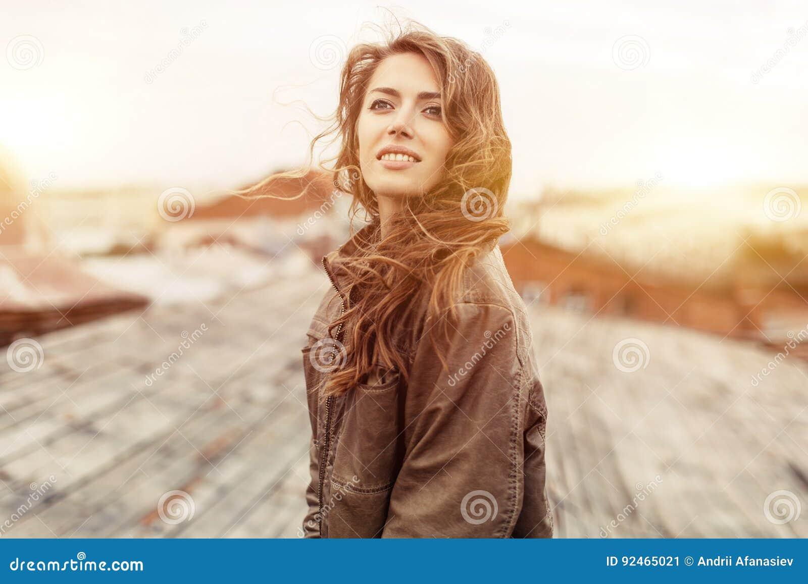 Mujer atractiva joven con buen humor que disfruta de paisaje hermoso de la ciudad mientras que se coloca en un tejado del edifici