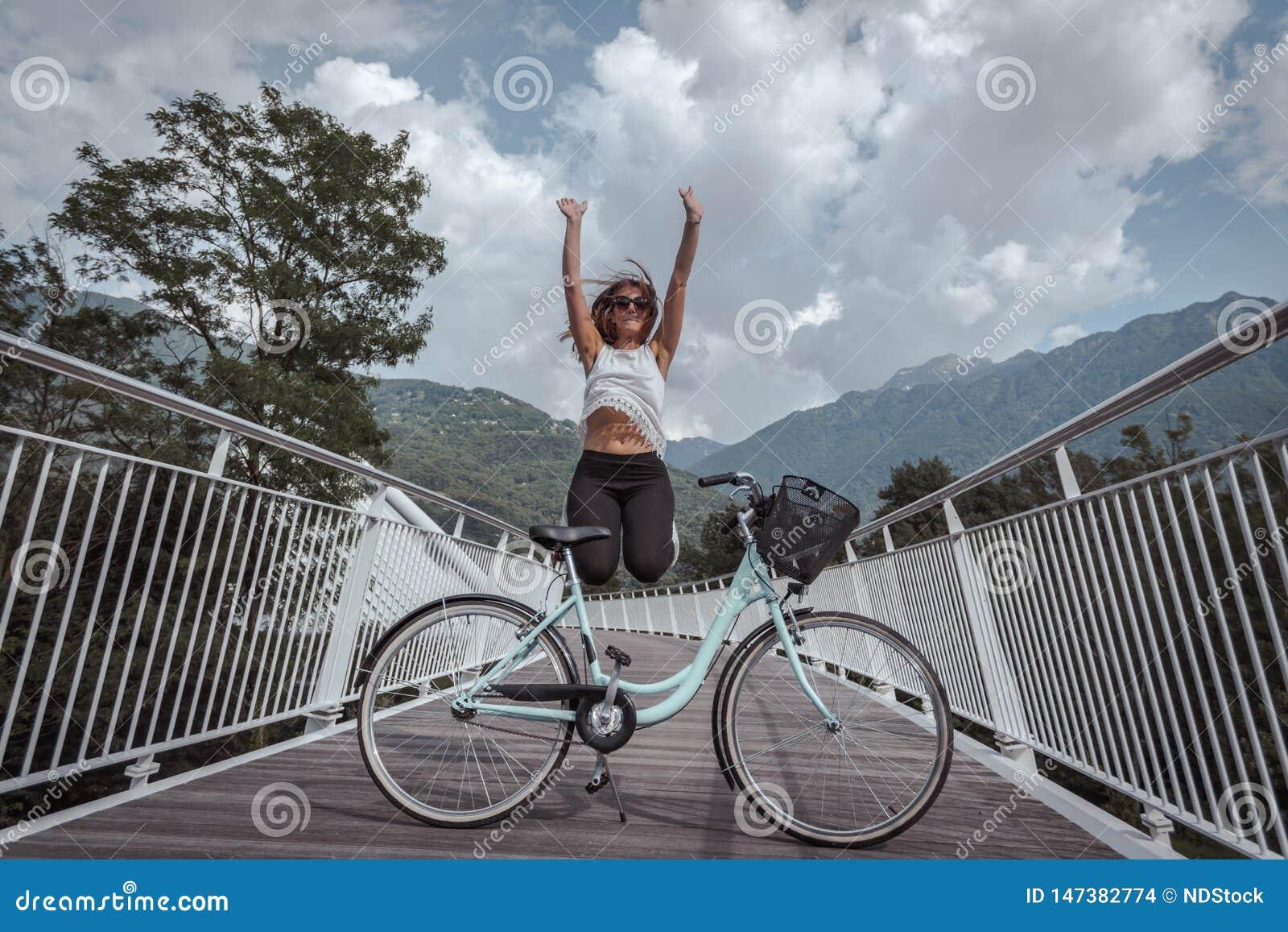 Mujer atractiva joven con la bicicleta en un puente