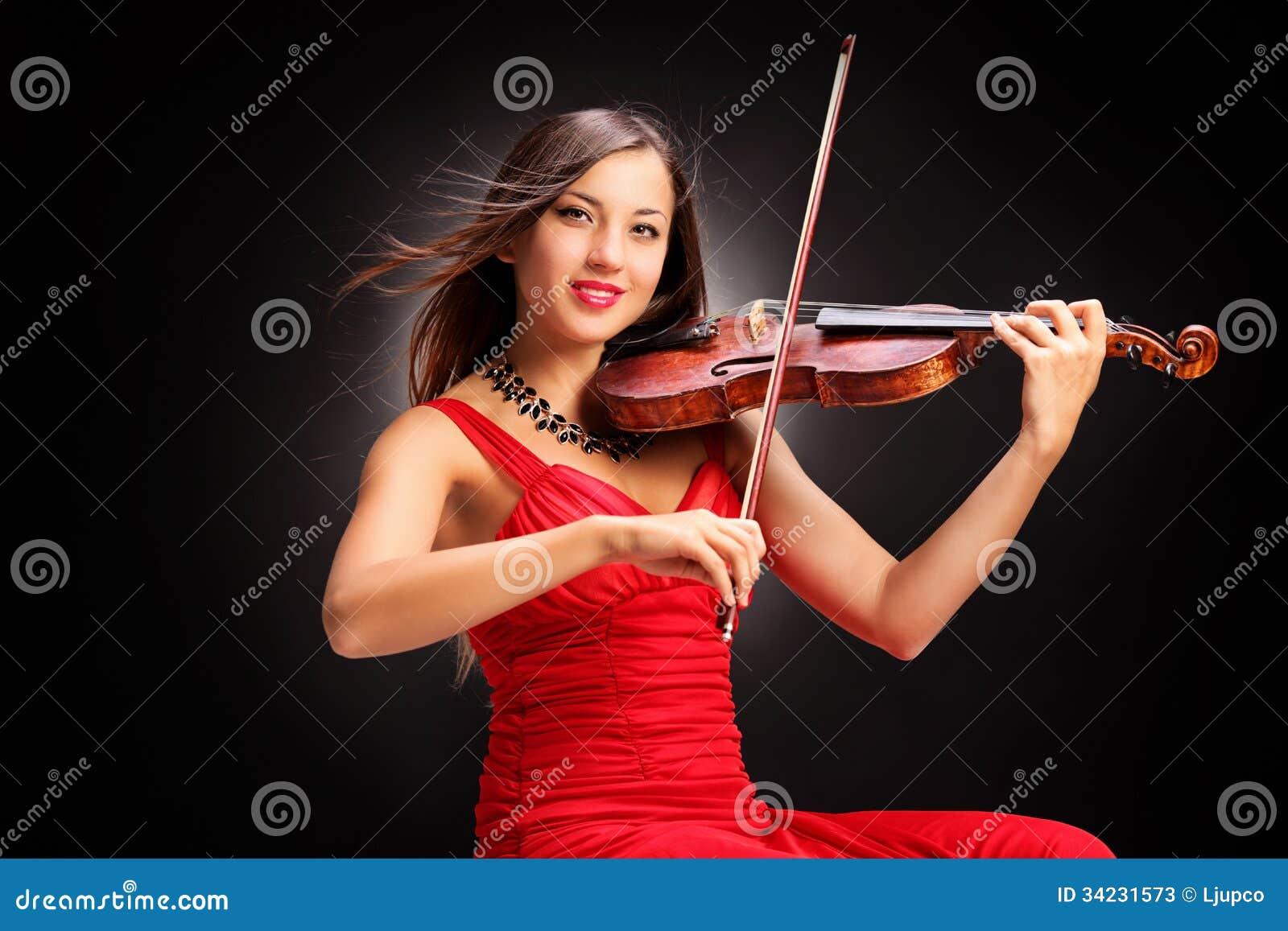 Mujer atractiva joven en el vestido rojo que toca el violín