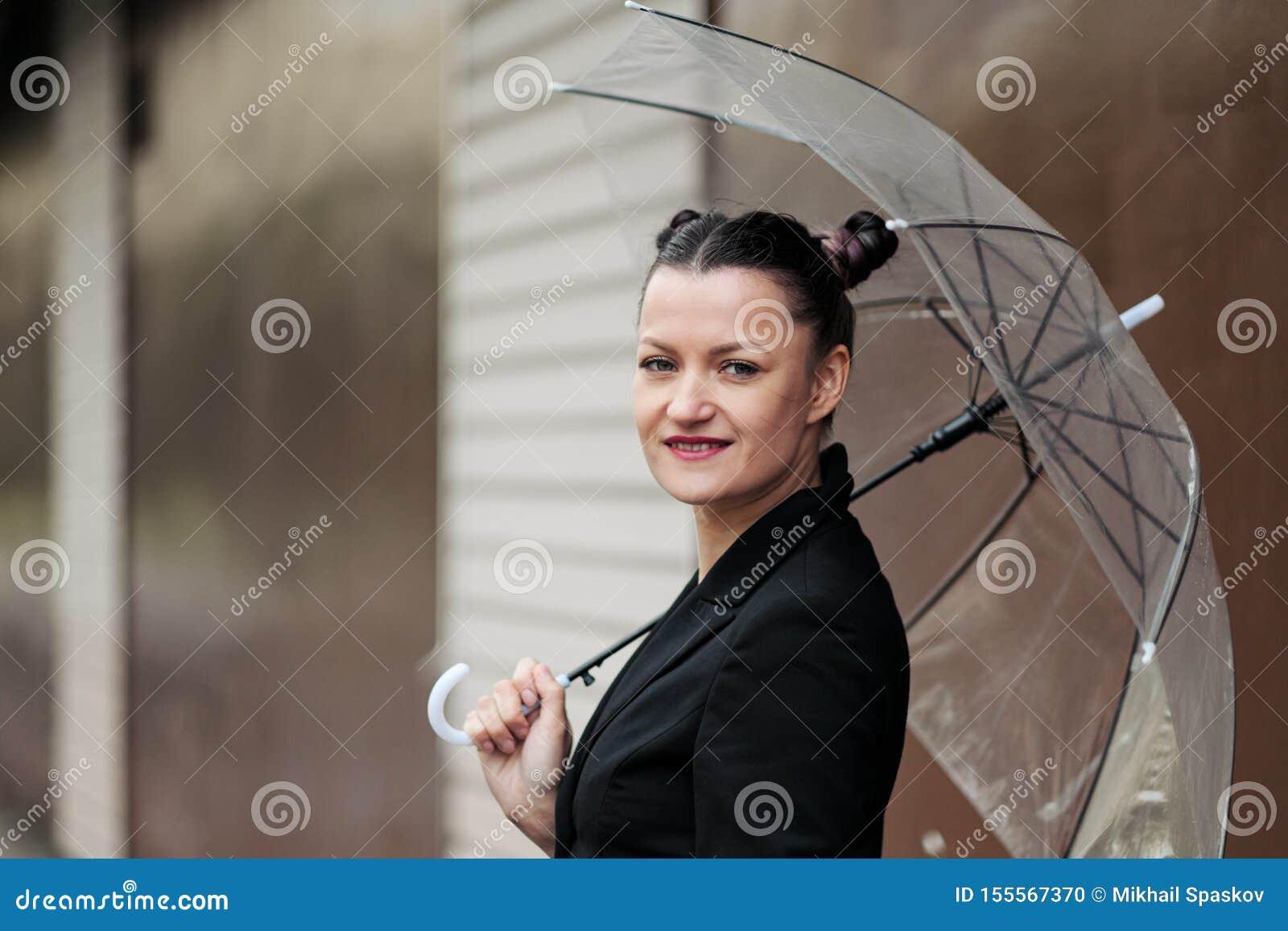 Mujer atractiva joven en la presentación negra de la chaqueta y de los tejanos al aire libre contra el fondo del edificio