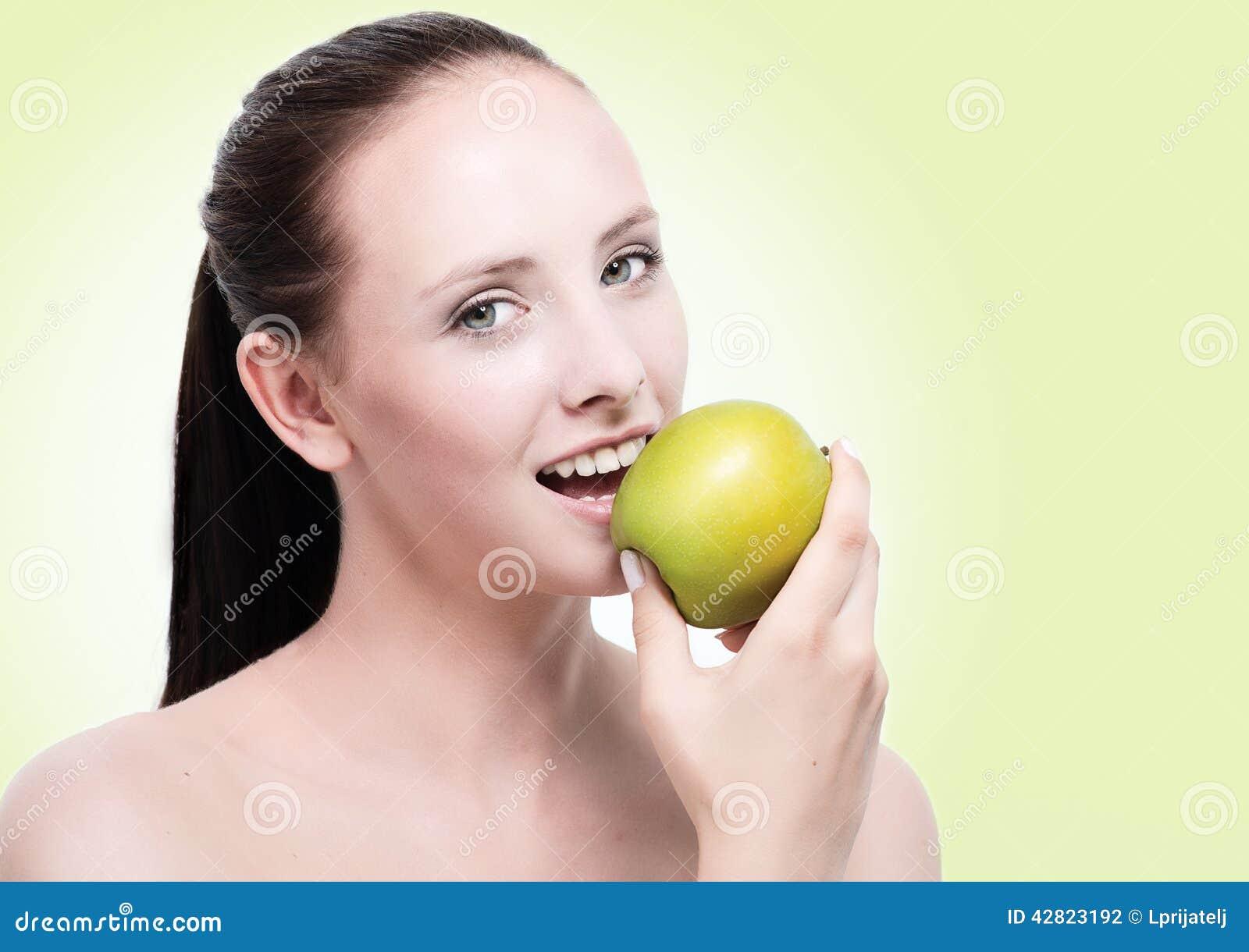 Mujer atractiva joven que come una manzana