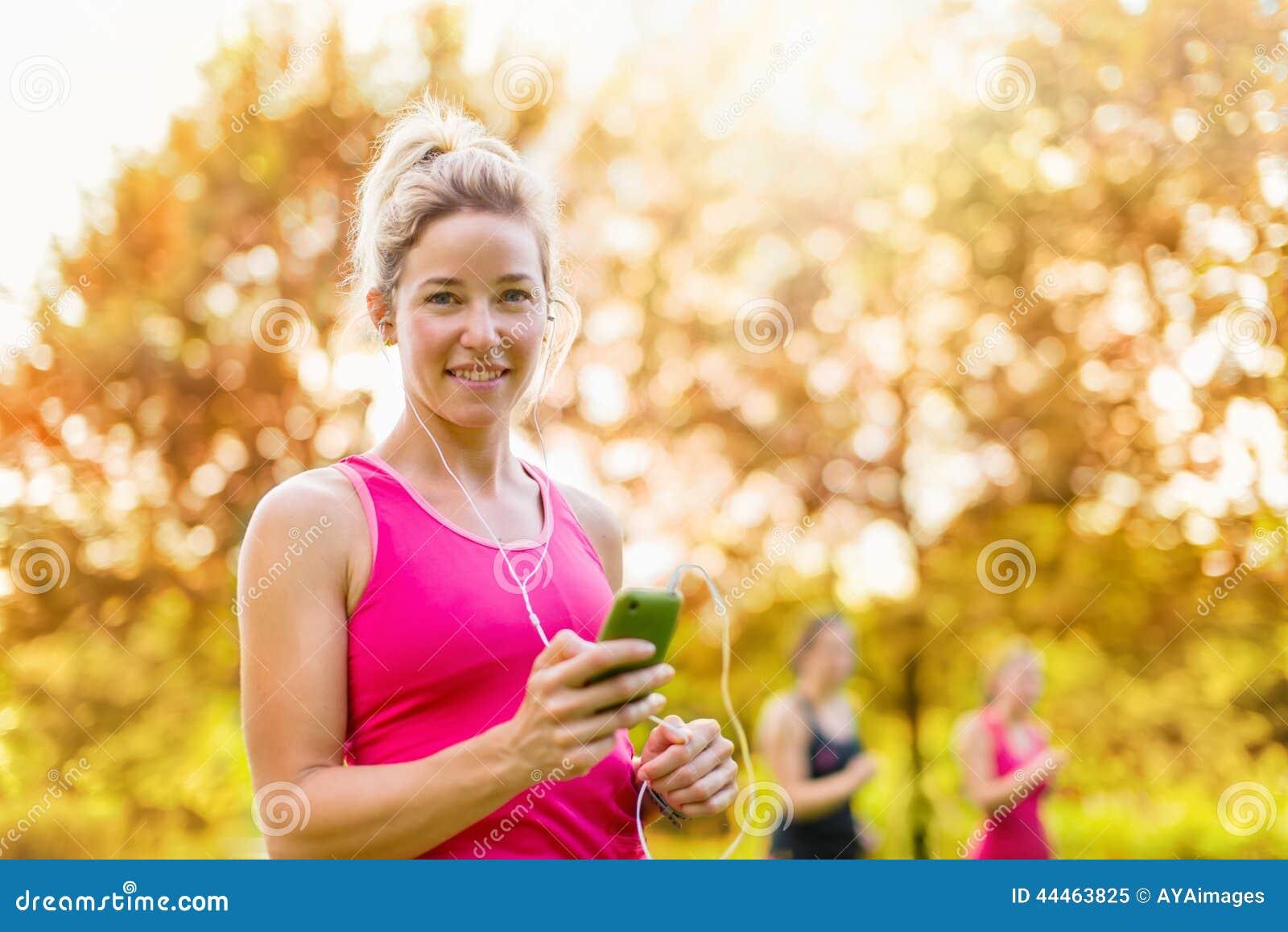 Mujer atractiva que escucha la música durante deporte