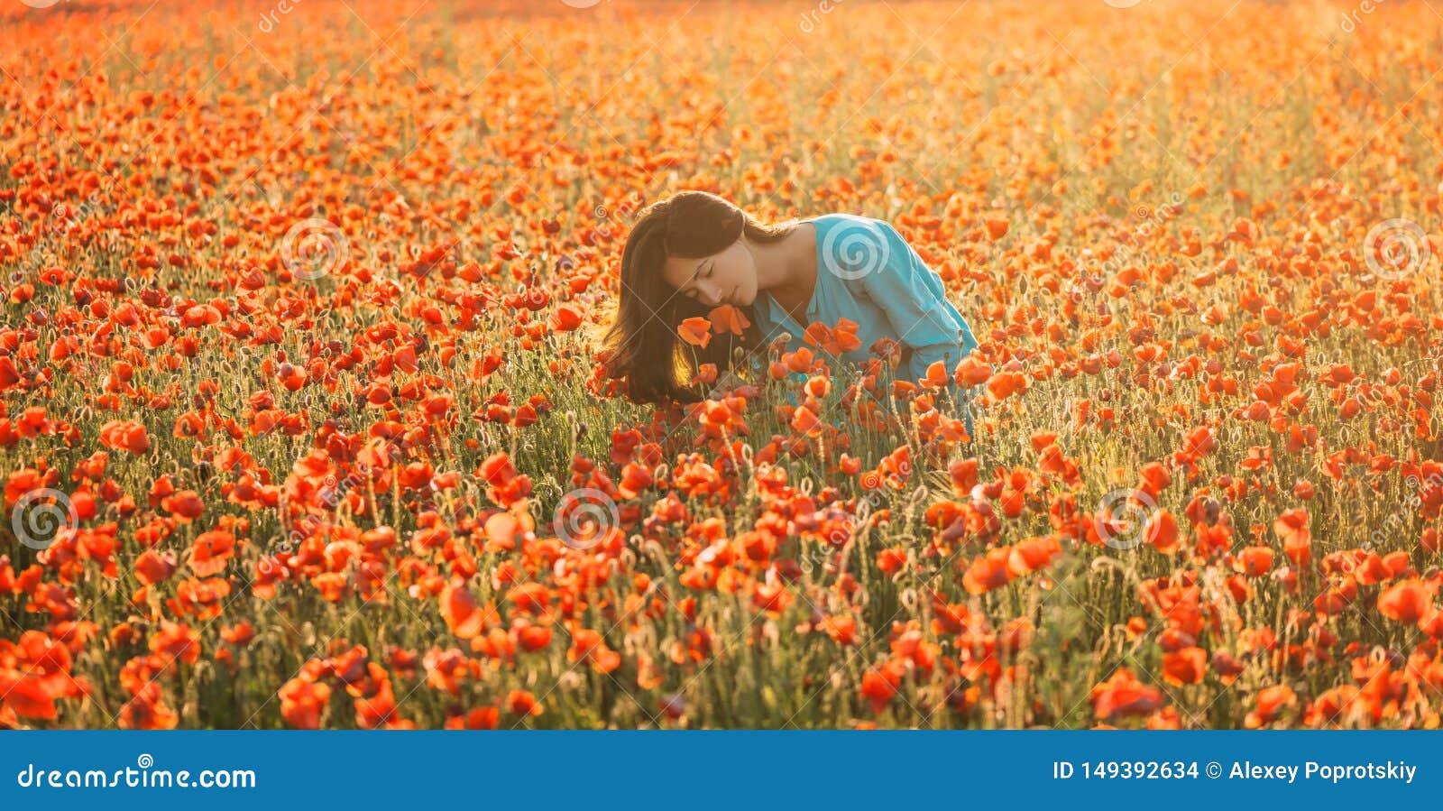 Mujer atractiva que huele una amapola en campo