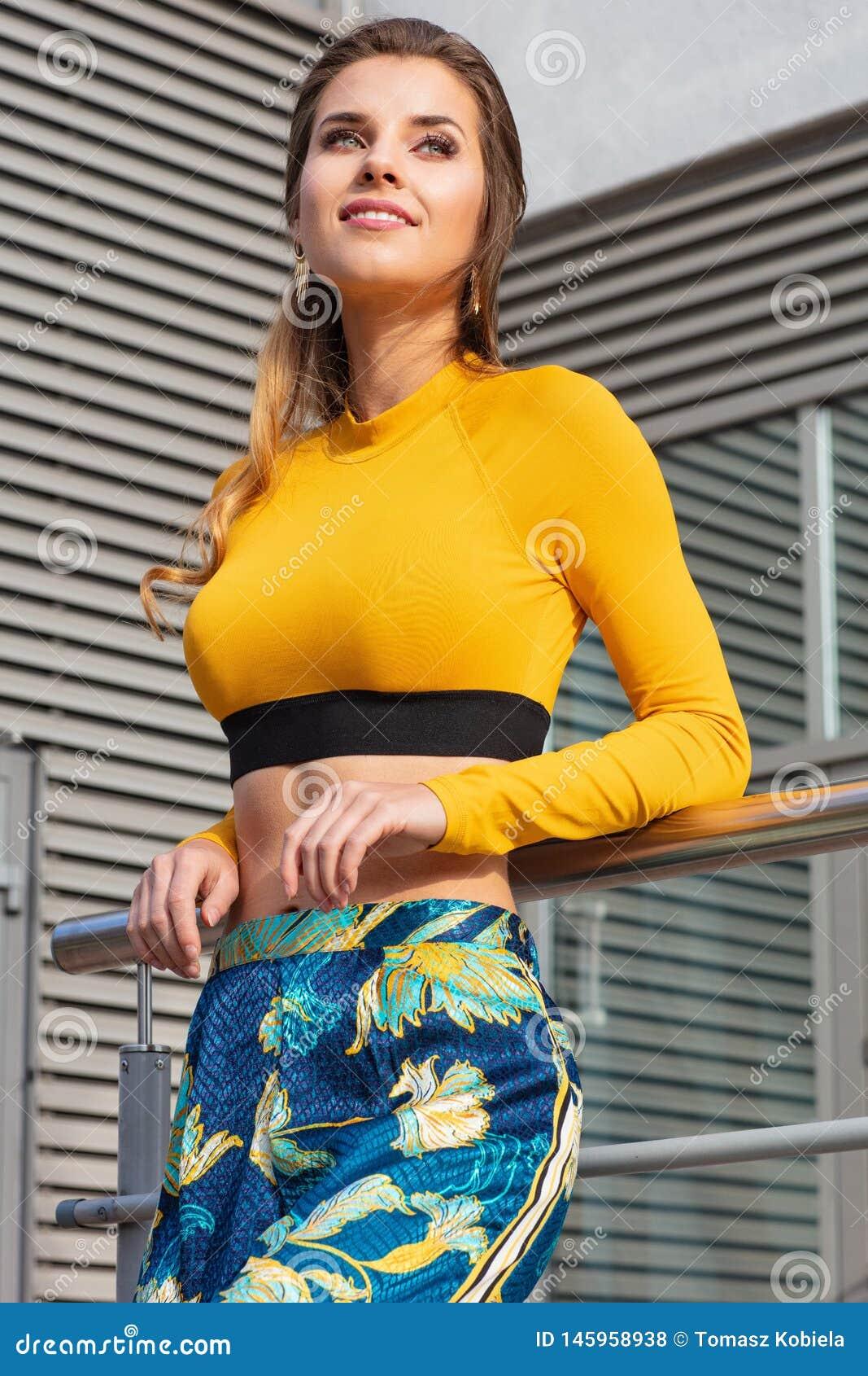 Mujer bastante atractiva y joven que presenta en la calle en ropa colorida