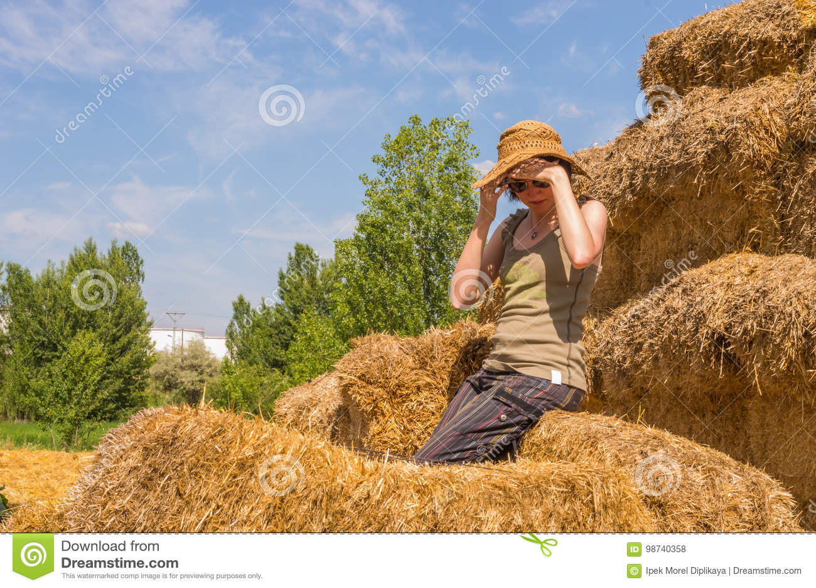 f999b0b185af2 Mujer bastante feliz con el sombrero que se sienta en una bala de la paja  que la cubre ojos con sus manos