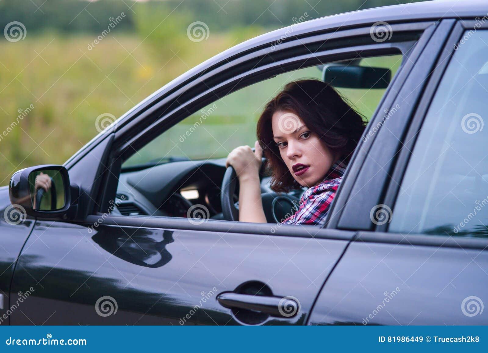 Mujer bastante joven que conduce su nuevo coche