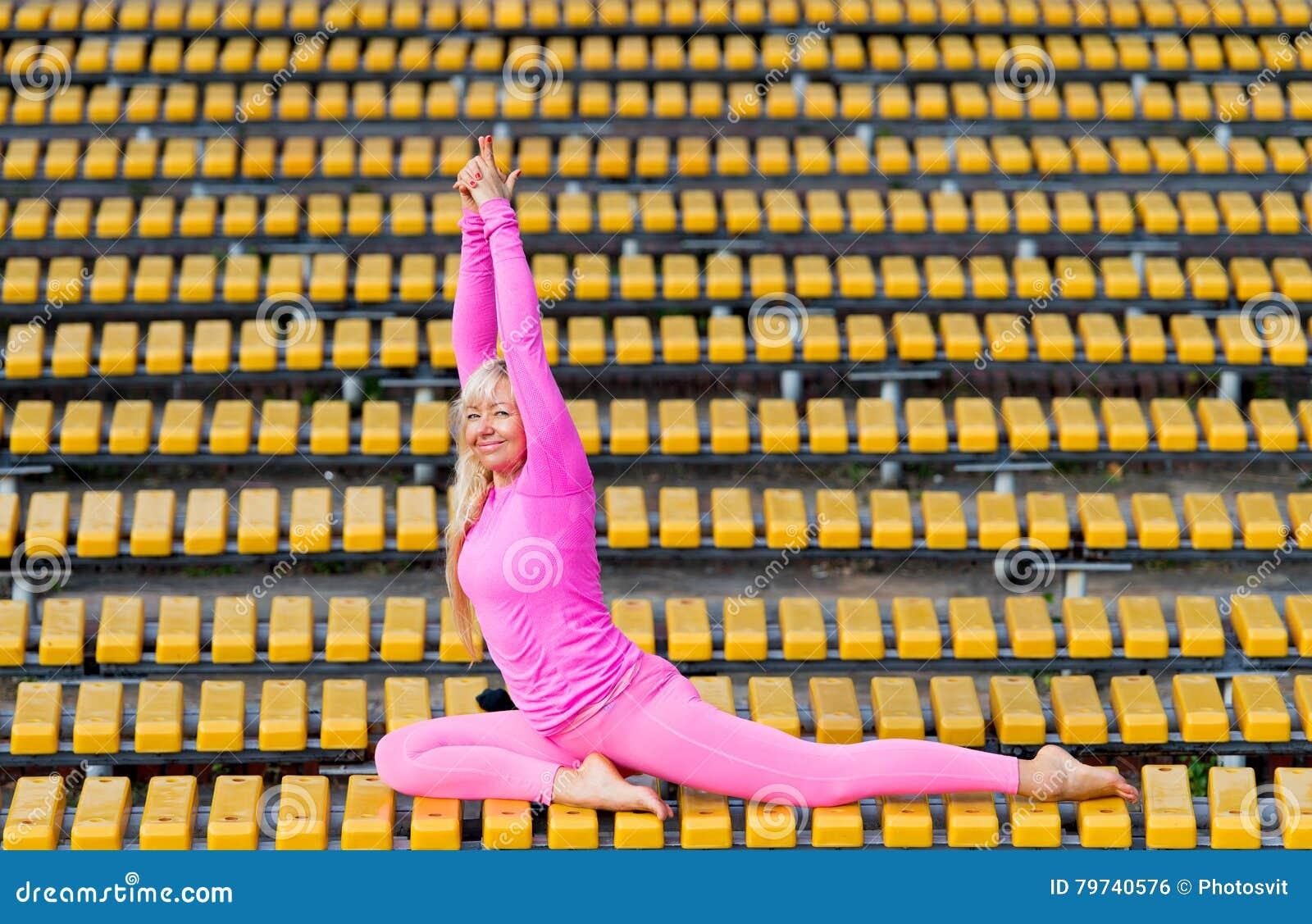 Mujer bastante joven que hace asanas de la yoga en el parque
