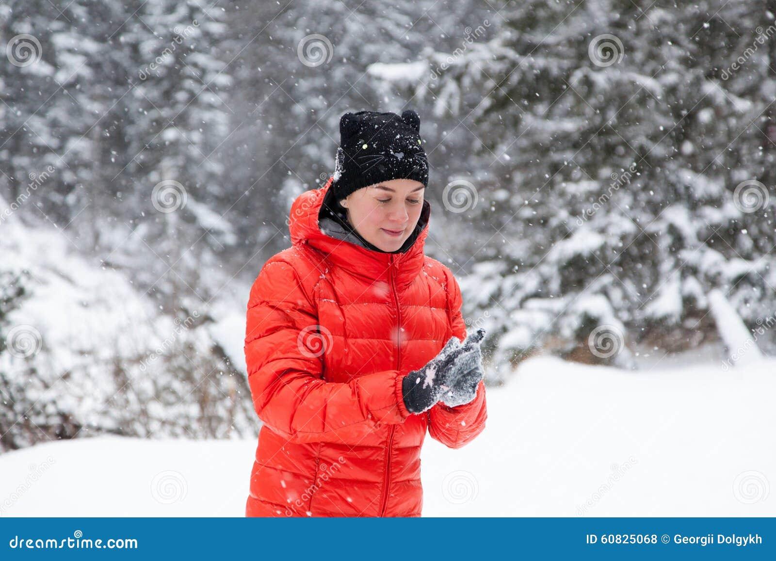 Mujer bastante joven que juega bolas de nieve