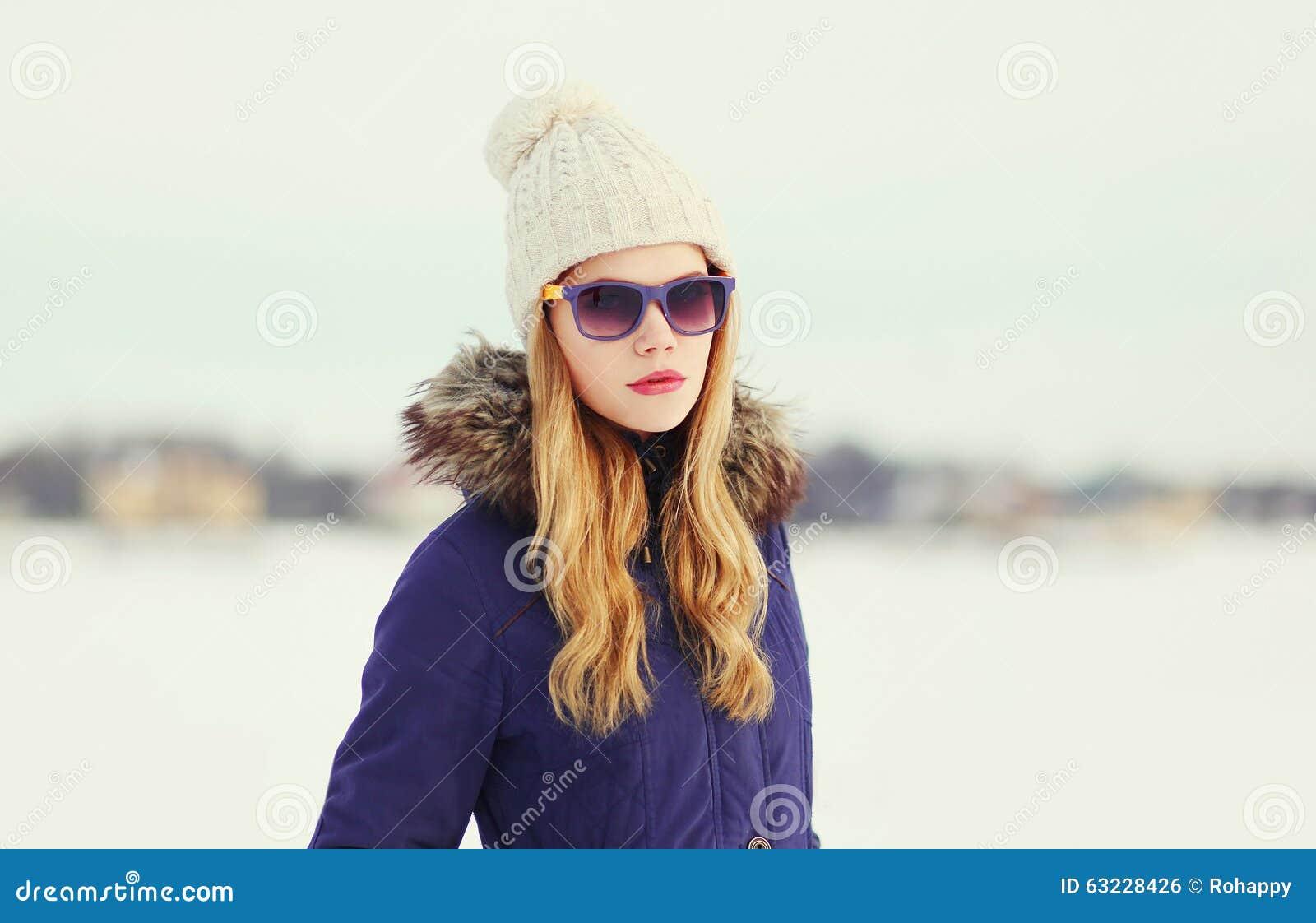 Mujer bastante rubia que lleva una chaqueta, un sombrero y gafas de sol