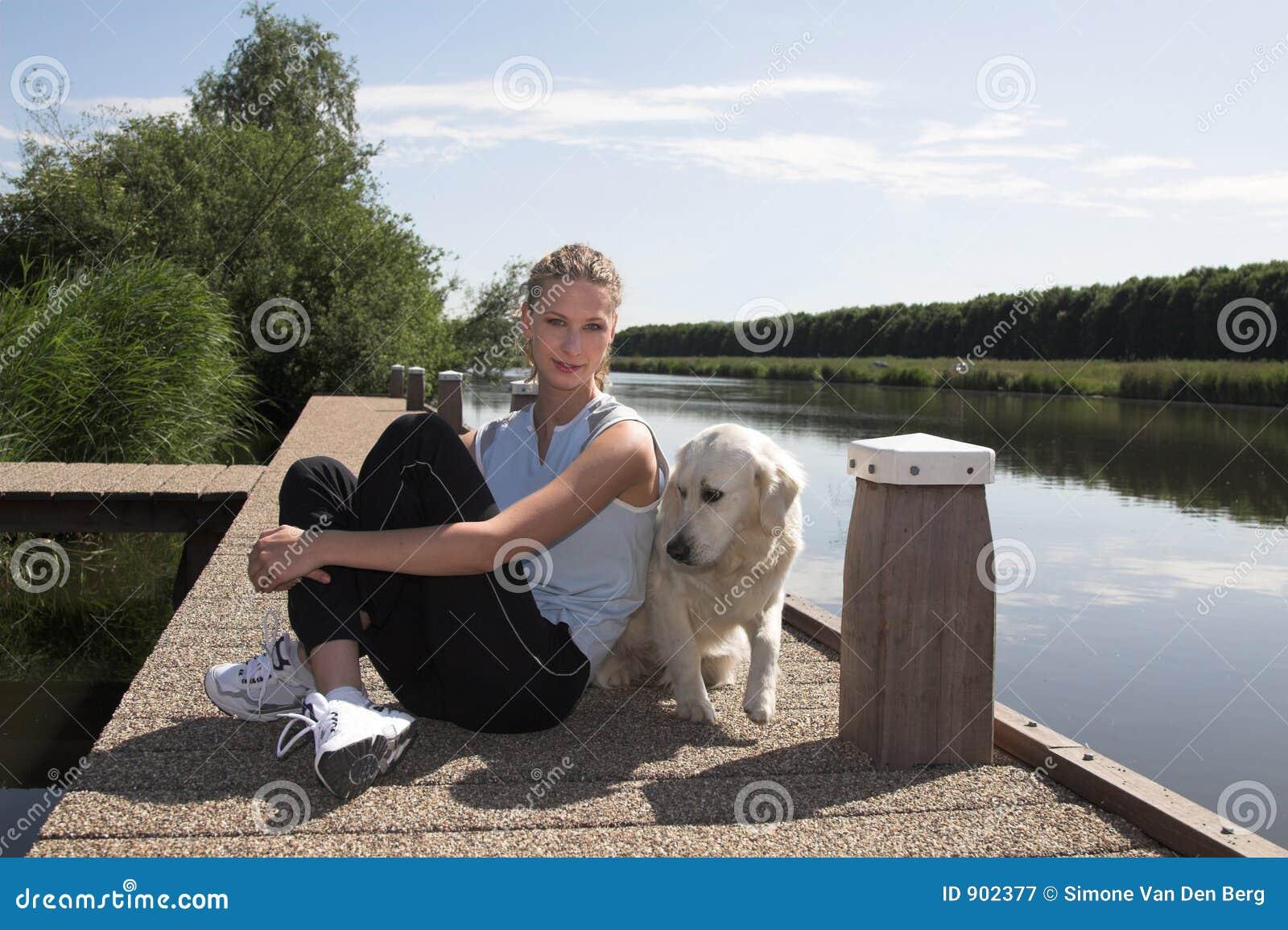 Mujer Bastante Rubia Que Se Relaja Con Su Perro Por La Orilla Del Agua