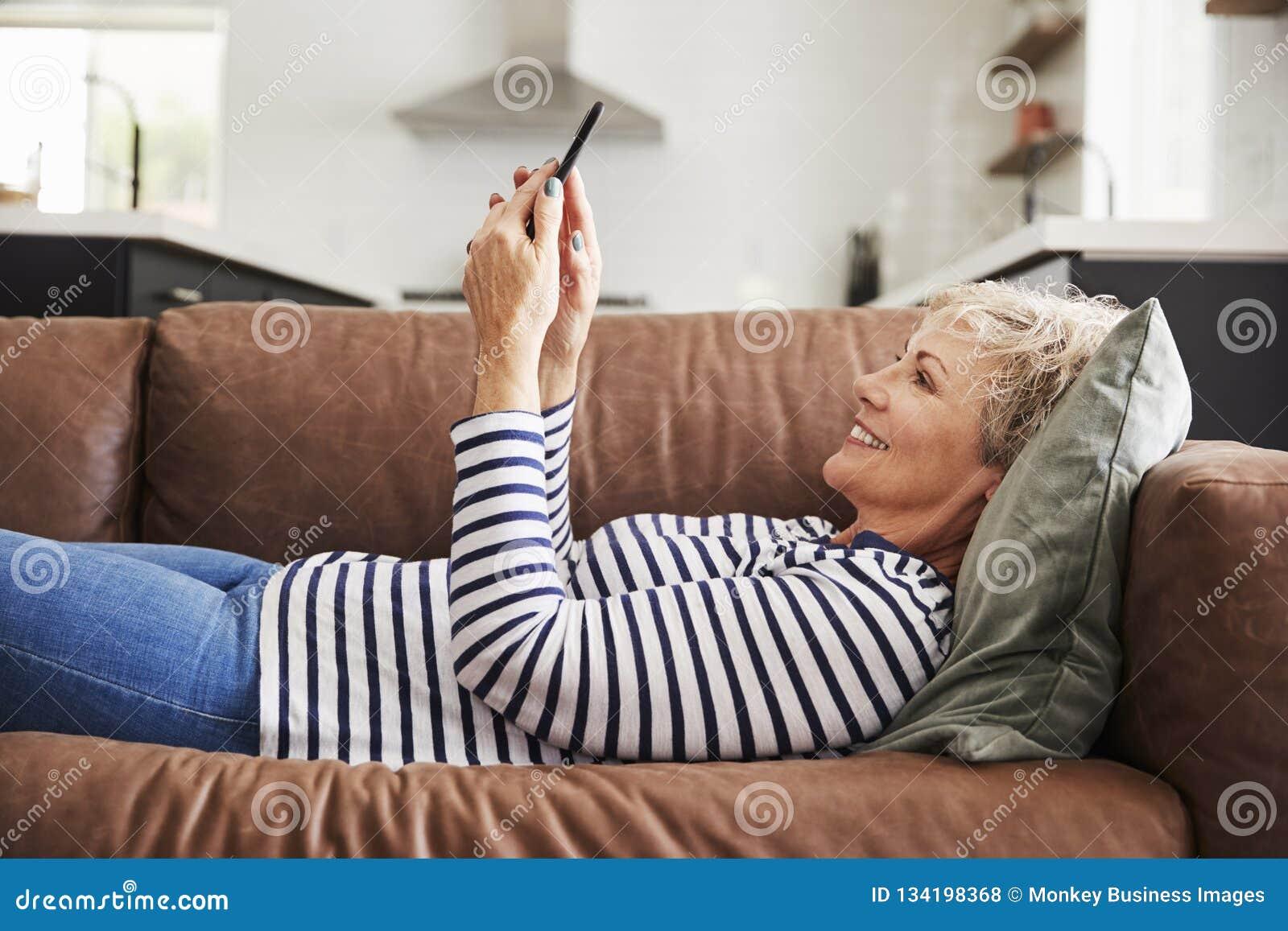 Mujer blanca mayor que miente en el sofá en casa usando smartphone