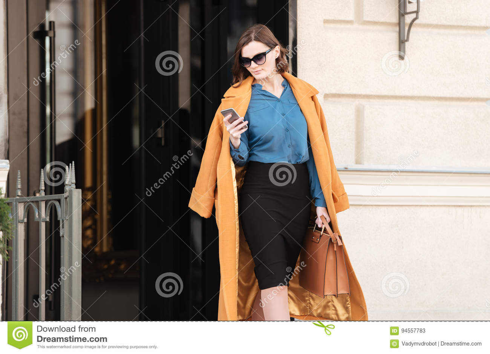 Mujer bonita confiada en gafas de sol usando el teléfono móvil
