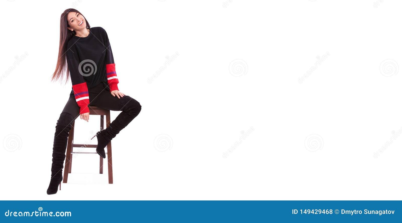 Mujer bonita en el traje negro aislado en el fondo blanco La morenita linda se sienta en la silla en el estudio blanco Ci?rrese e