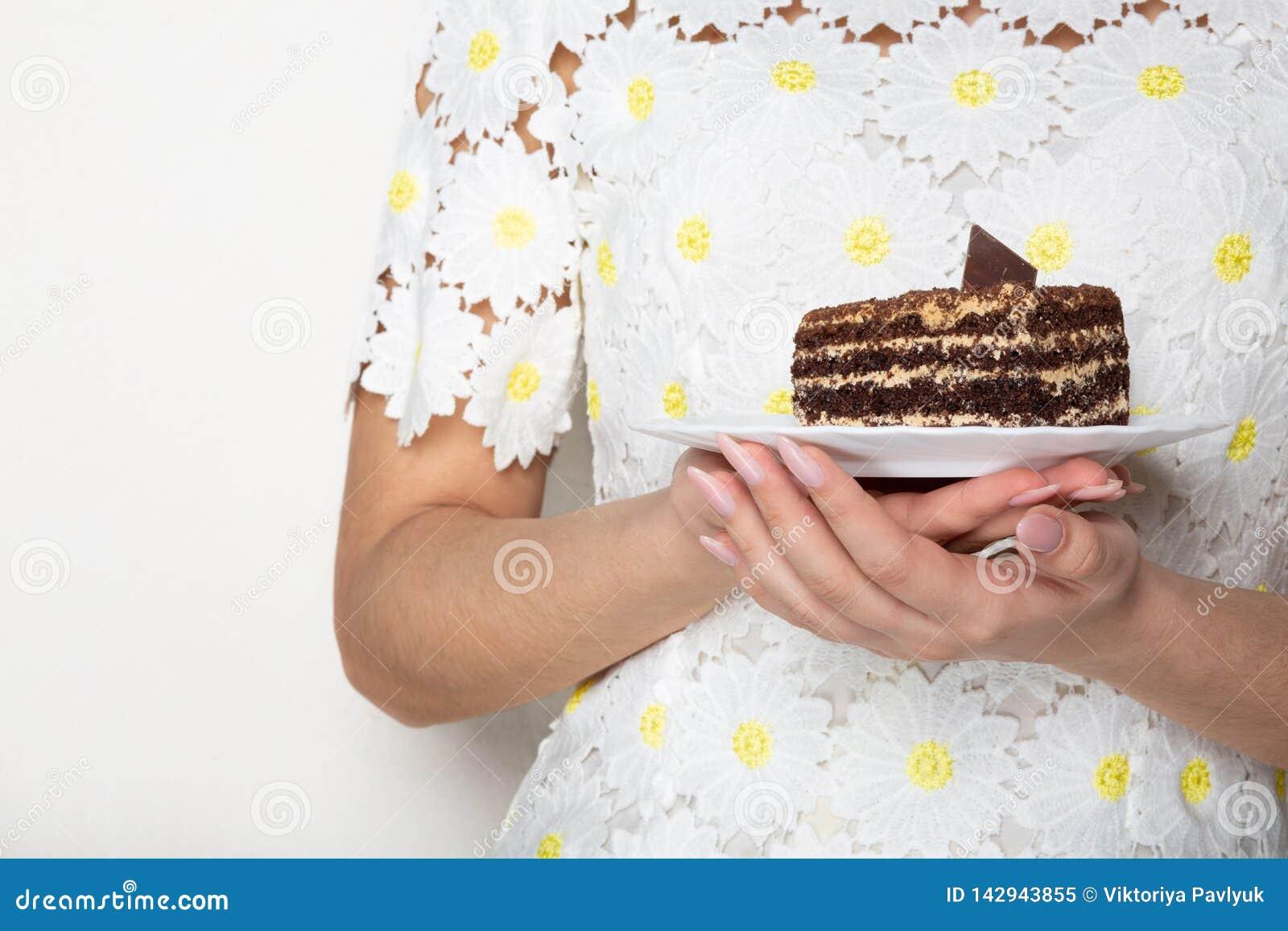 Mujer bonita en el vestido de moda que sostiene una placa con la torta de chocolate sabrosa Espacio para el texto