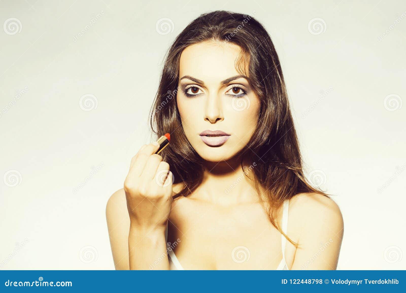9e9c15e0f85e Mujer joven con maquillaje en cara bonita y el pelo moreno largo en  sujetador blanco atractivo en el cuerpo que sostiene el lápiz labial rojo  de moda en ...