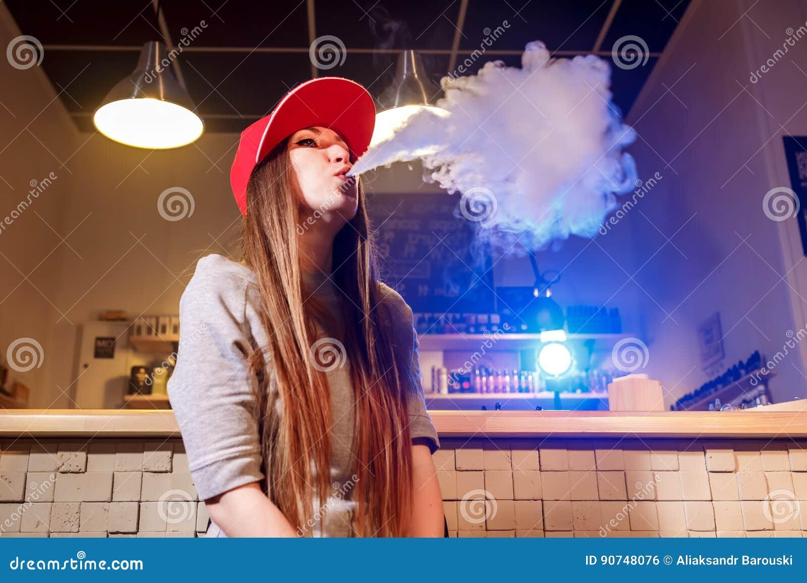 Mujer bonita joven en humo rojo del casquillo un cigarrillo electrónico en la tienda del vape