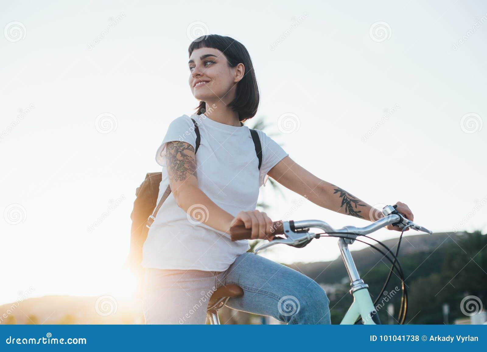 Mujer bonita linda en la bicicleta en puesta del sol