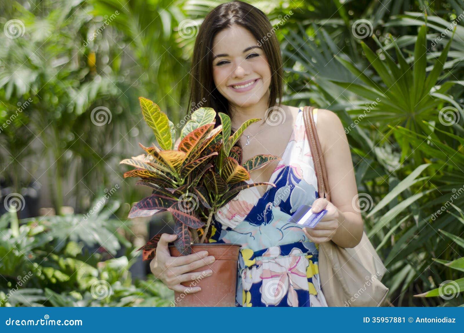 Mujer bonita que compra algunas plantas