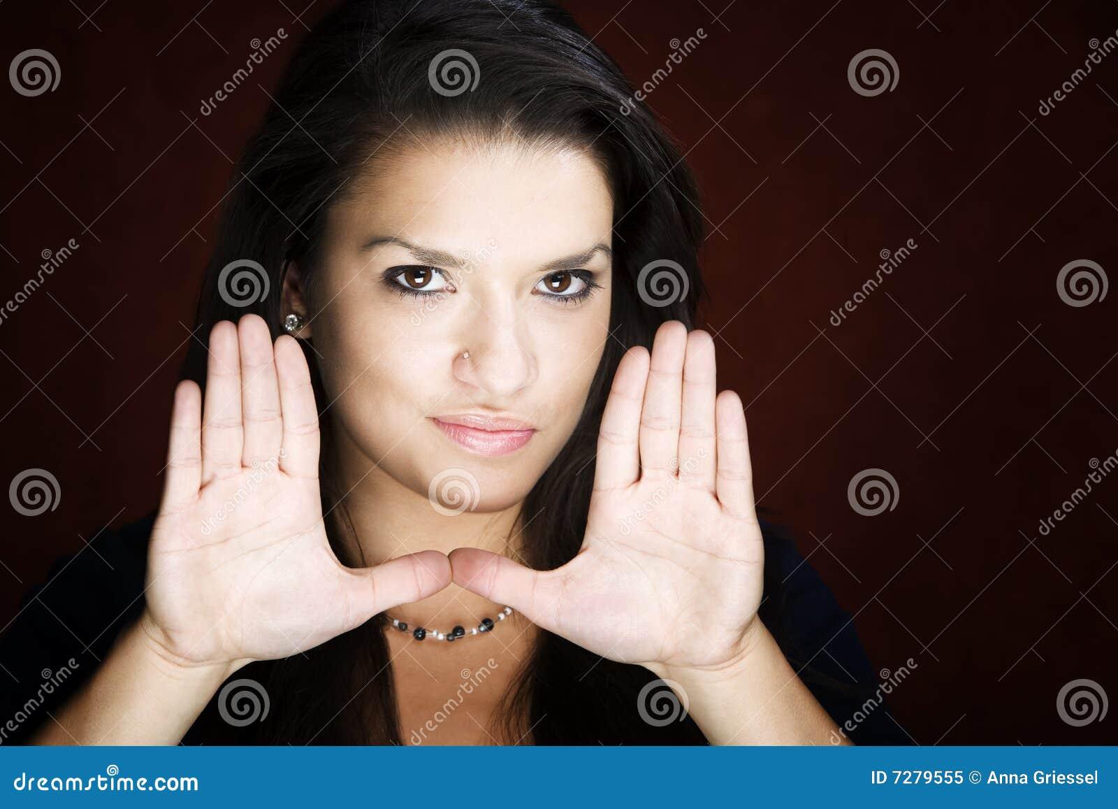 Mujer bonita que enmarca su cara