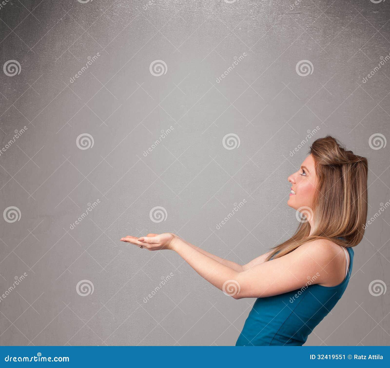 Mujer bonita que presenta un espacio vacío de la copia