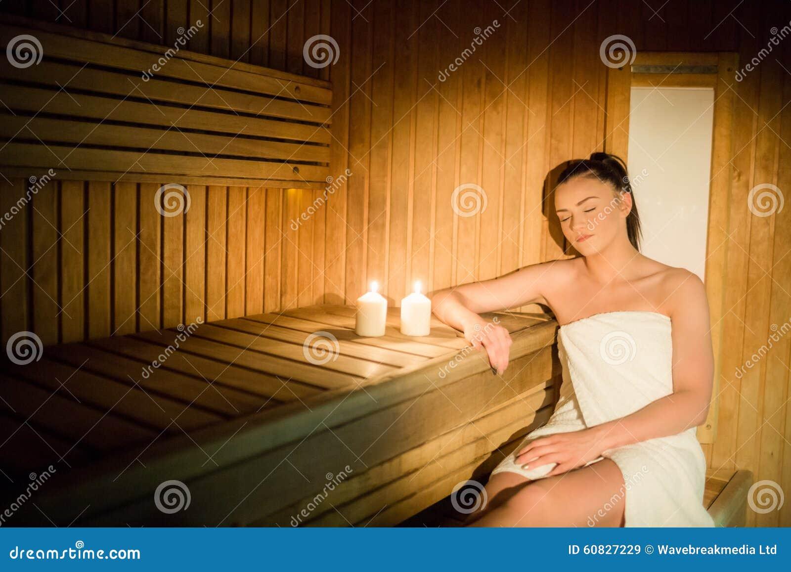 Mujer bonita que se relaja en la sauna