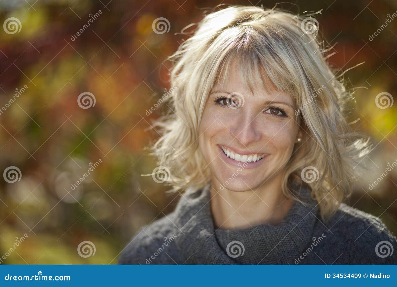 Mujer bonita que sonríe en un bosque