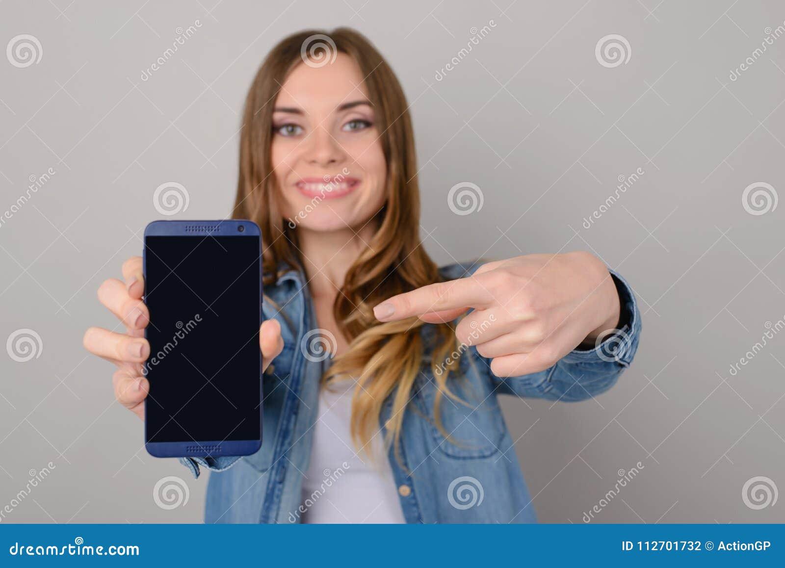 Mujer bonita sonriente que muestra la pantalla vacía negra de su smartphone y que señala en ella con su finger; aislado en fondo