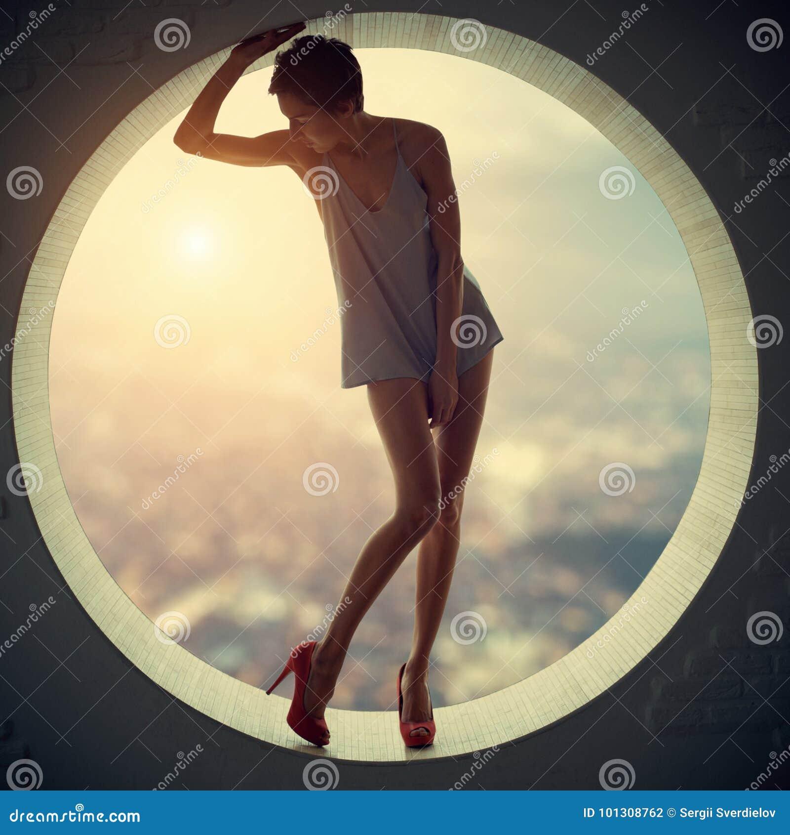 Mujer bonita y atractiva delgada adulta joven hermosa de la sensualidad en vestido de moda de la elegancia en una ventana redonda