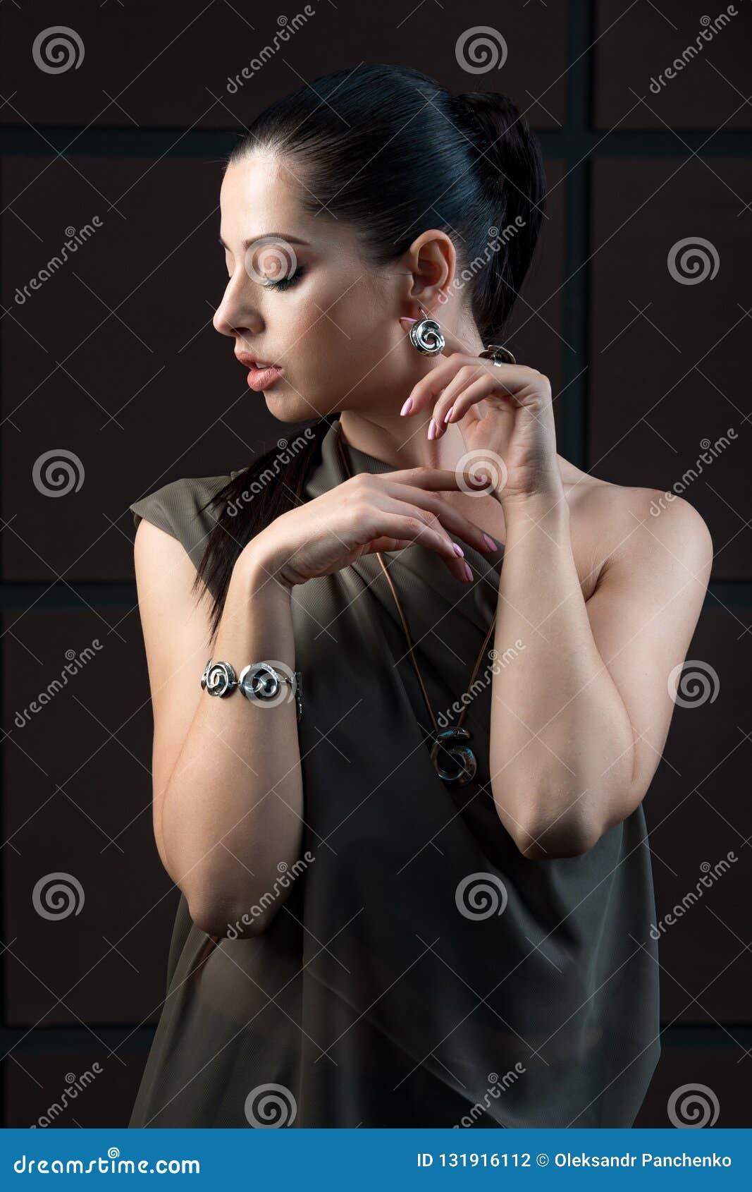 Mujer cabelluda oscura sofisticada hermosa que lleva llamativo elegante
