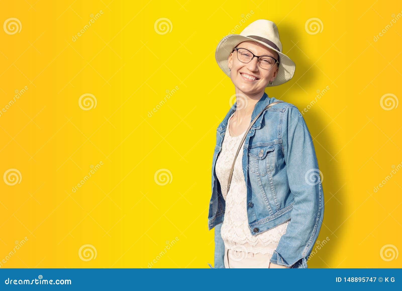 Mujer calva cauc?sica joven feliz en sombrero y ropa casual que disfruta de vida despu?s de sobrevivir el c?ncer de pecho Retrato