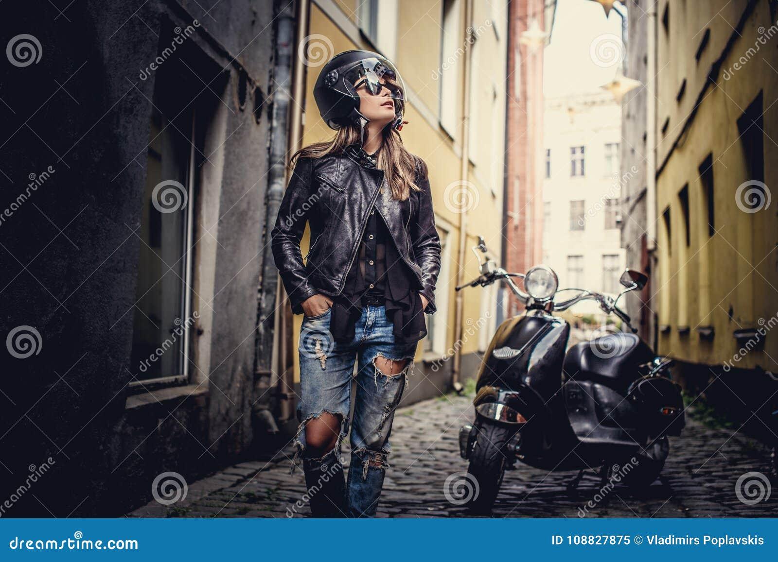 Mujer casual impresionante que presenta con el scoote del moto