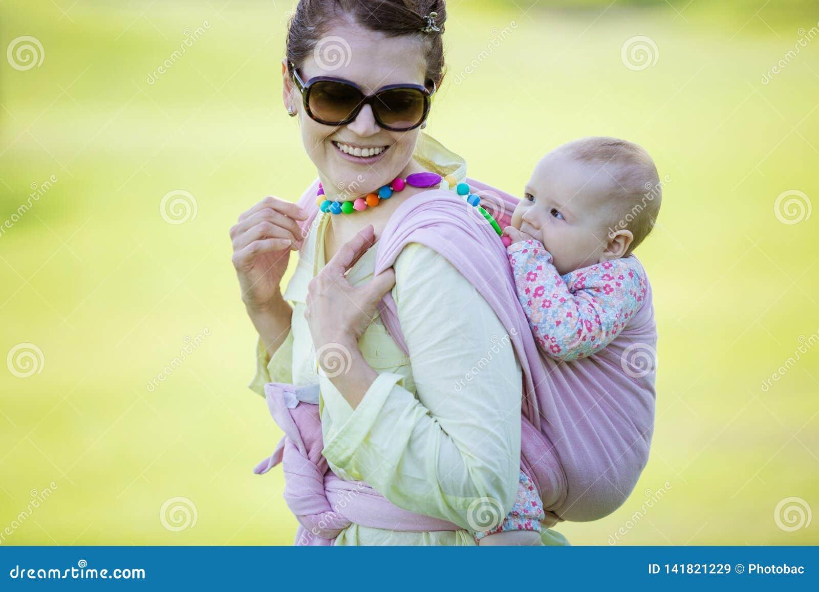 Mujer caucásica alegre que lleva a su hija del bebé en la parte posterior en parque de la primavera