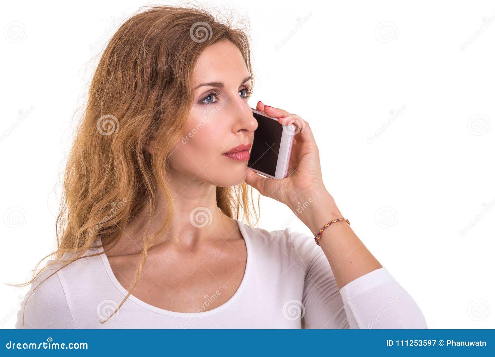 Mujer caucásica hermosa en la camiseta blanca usando smartphone stu