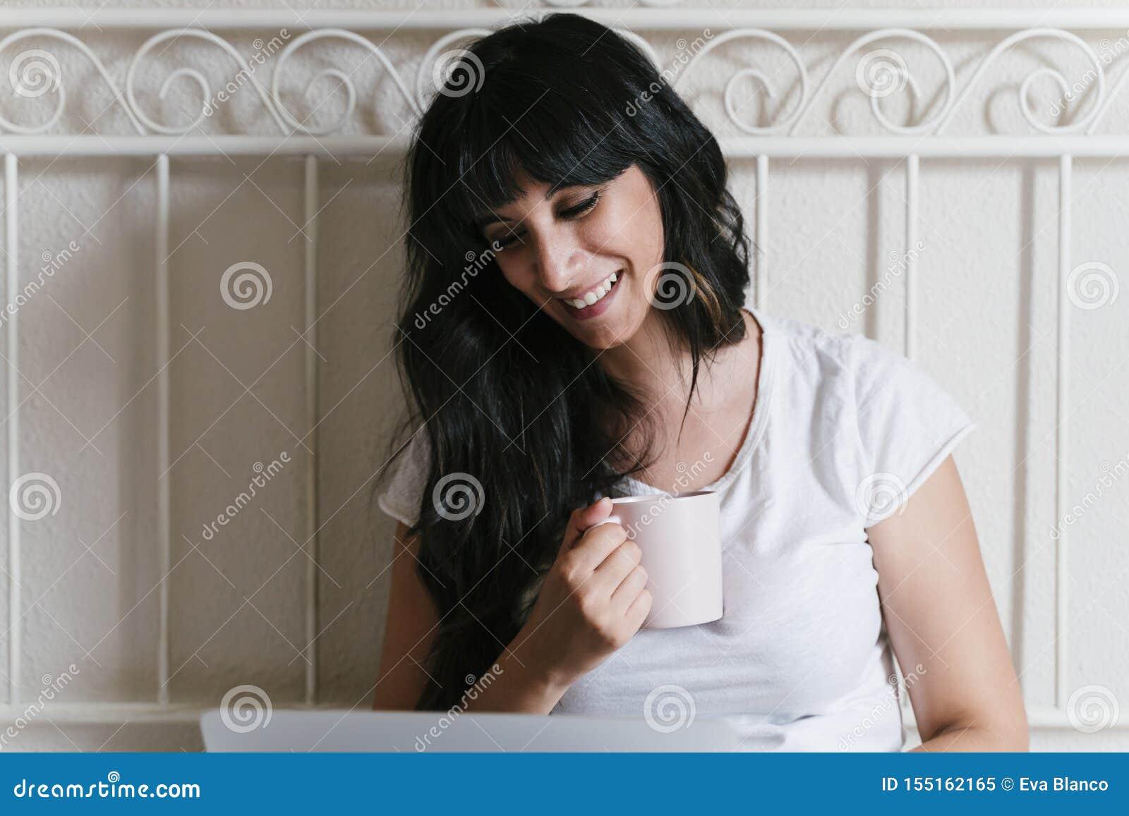 Mujer caucásica joven en casa en la cama que come una taza de café o de té Trabajo en el ordenador port?til Mañana y relajar conc
