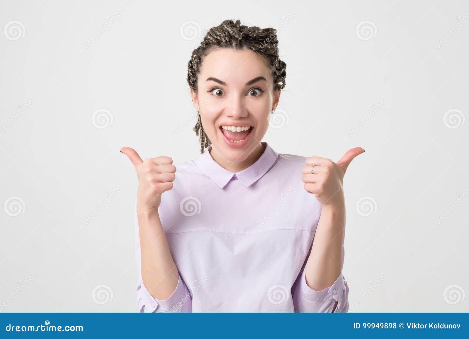 Mujer caucásica joven feliz que da los pulgares para arriba en el fondo blanco