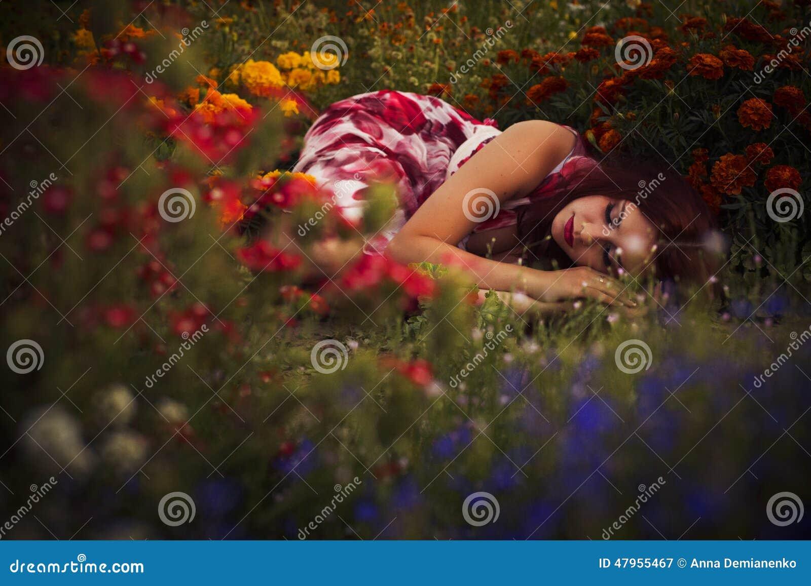Mujer caucásica morena en el vestido blanco y rojo en el parque en flores rojas y amarillas en un baile de la puesta del sol del