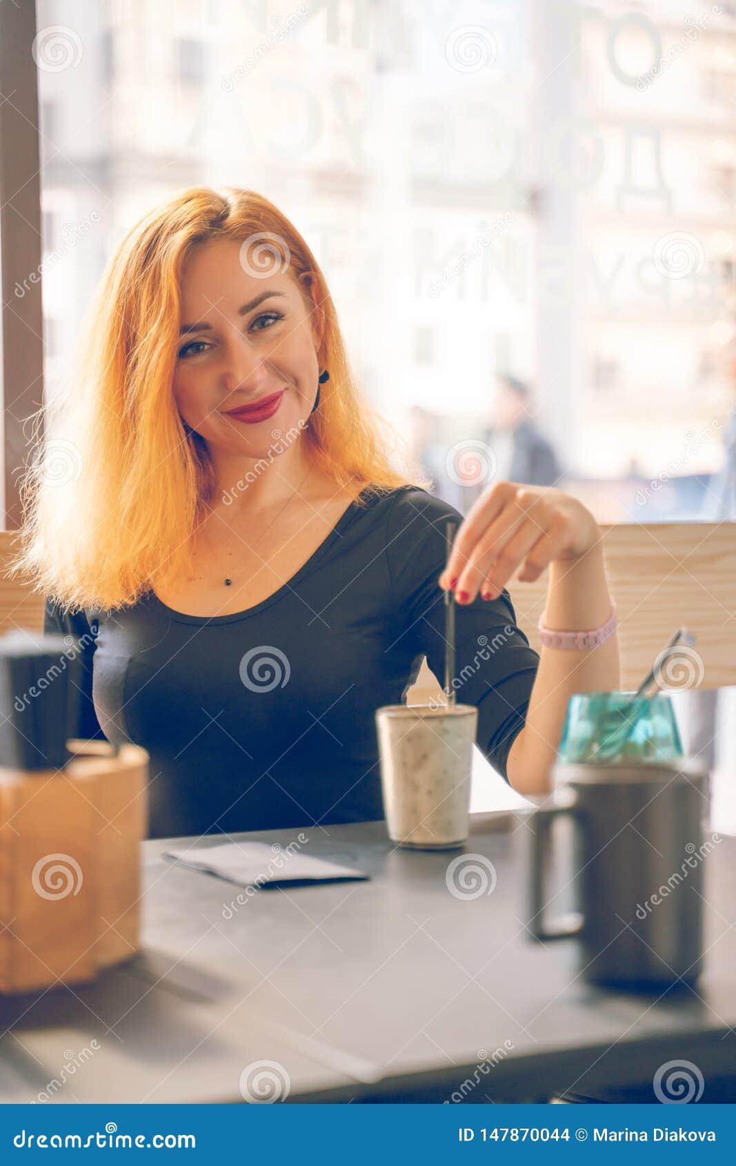Mujer caucásica redheaded feliz bonita en la taza negra de las bebidas de la camisa de café en el café moderno solamente