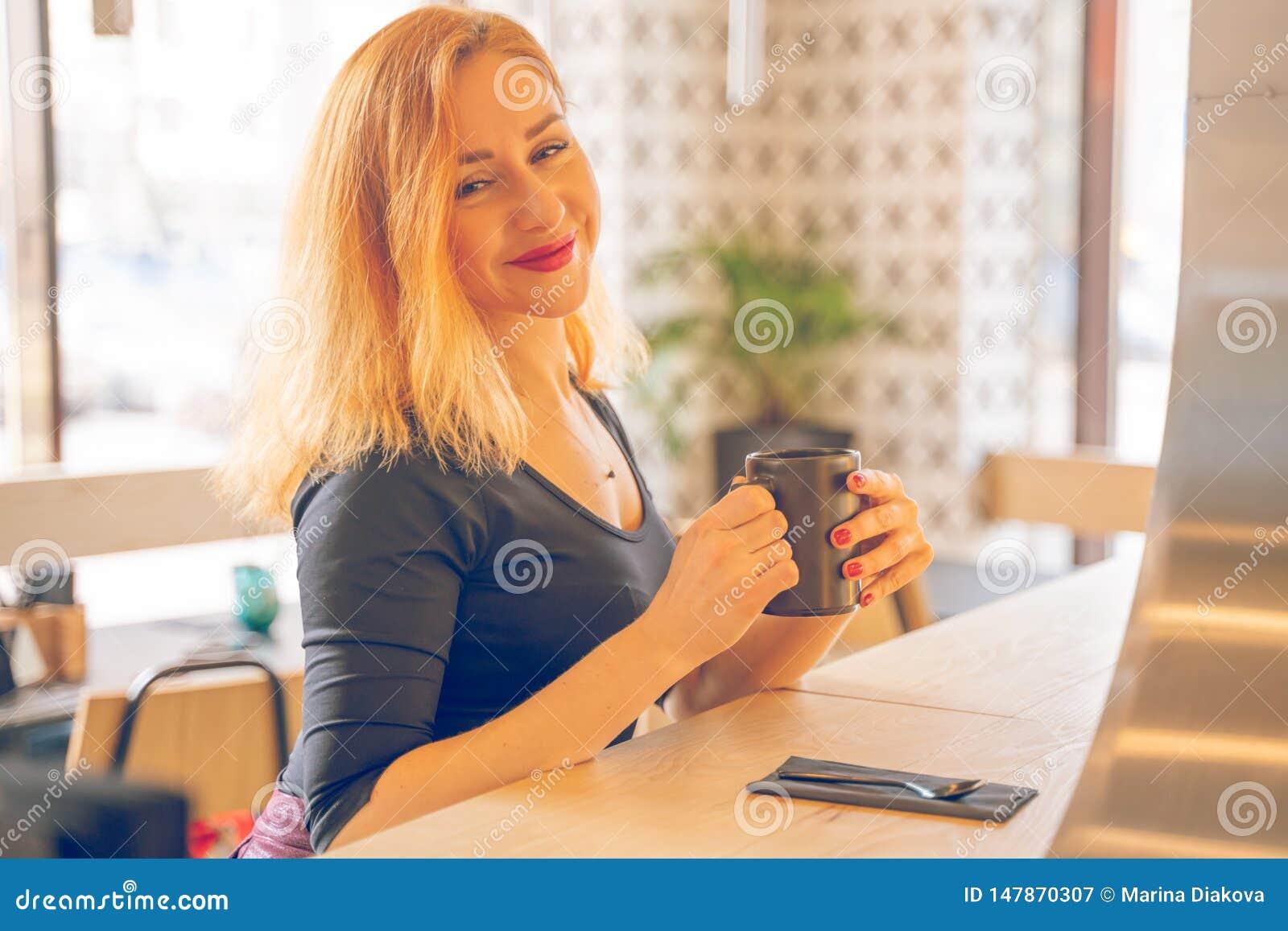 Mujer cauc?sica redheaded feliz bonita en la taza negra de las bebidas de la camisa de caf? en el caf? moderno solamente