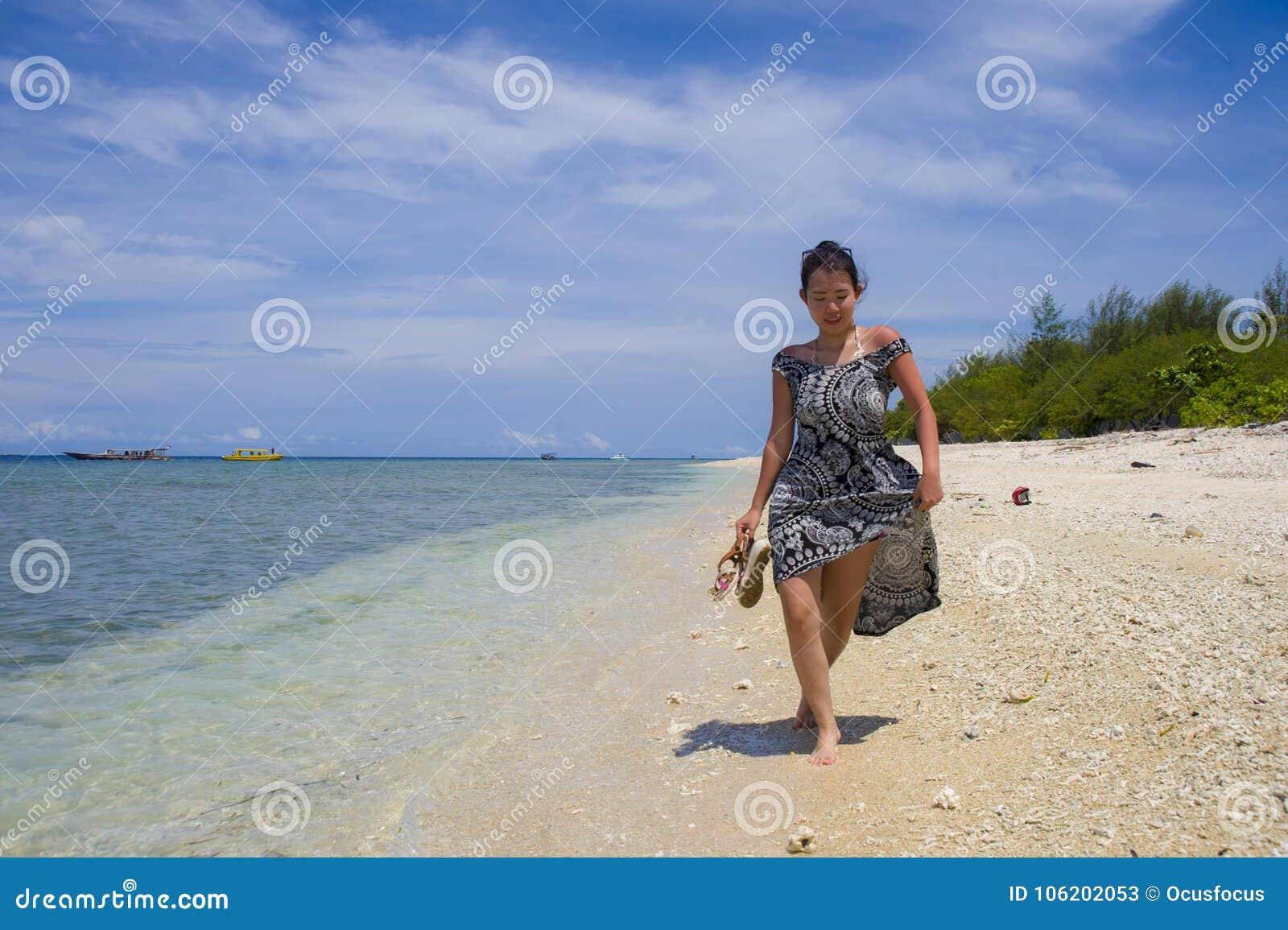 Mujer china asiática feliz en vestido del verano que camina en la playa hermosa de la isla de Tailandia debajo de un cielo azul e