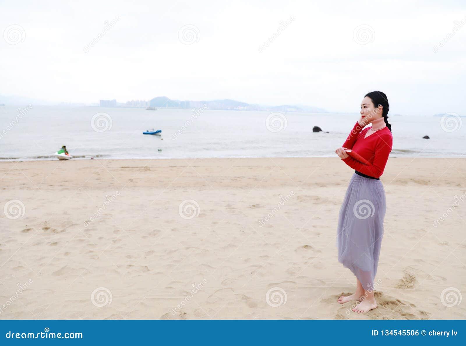 Mujer china asiática joven con el libro y escuchar el paseo de la música a lo largo de la playa de la arena