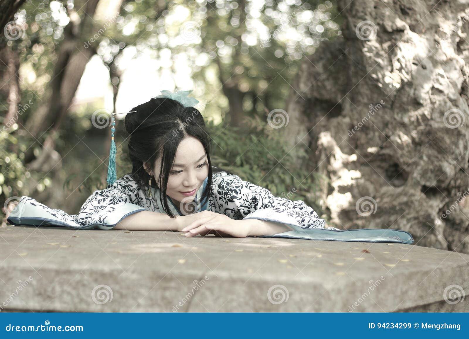 Mujer china en subida azul y blanca tradicional del vestido de Hanfu sobre la tabla de piedra