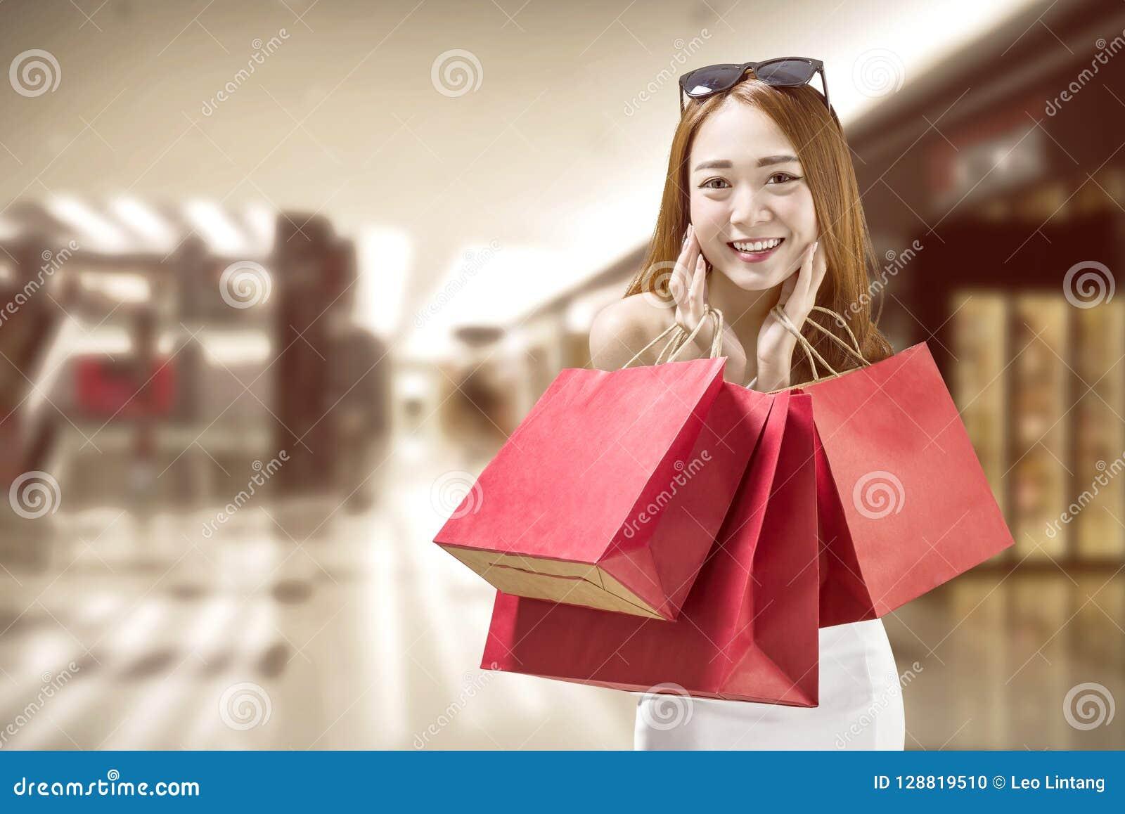 Mujer china feliz con las bolsas de papel rojas en la alameda