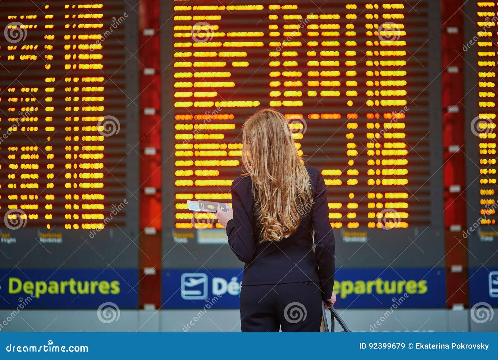Mujer con bulto de mano en el terminal de aeropuerto internacional, mirando al tablero de la información