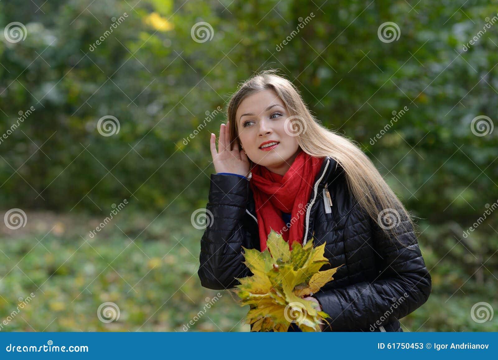 Mujer con chisme que escucha de las hojas de otoño a disposición